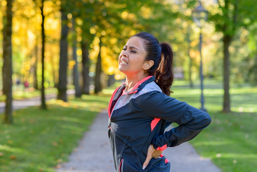woman holding her painful back after exercising in park
